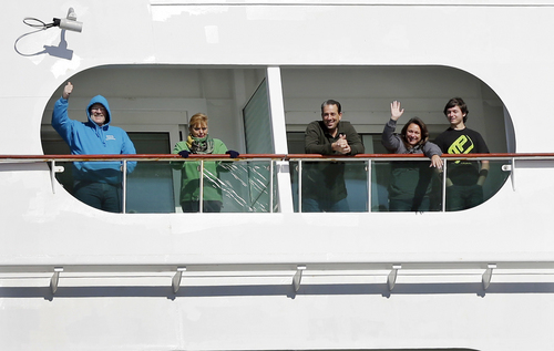 Passengers wave from the Explorer of the Seas cruise ship as it docks at a berth in Bayonne, N.J., Wednesday, Jan. 29, 2014. The number of passengers and crew reported stricken ill on the cruise ship has risen to nearly 700. The U.S. Centers for Disease Control and Prevention said Wednesday its latest count puts the number of those sickened aboard the Explorer of the Seas at 630 passengers and 54 crew members. (AP Photo/Mel Evans)