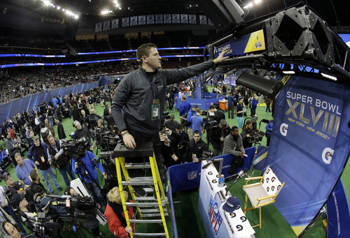 Jeremy Krug changes a sign as the Seattle Seahawks get ready to start their media day for the NFL Super Bowl XLVIII football game Tuesday, Jan. 28, 2014, in Newark, N.J. (AP Photo/Charlie Riedel)