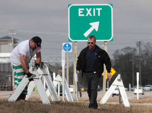 David Hansen of Gulfport, Miss., police, right, and state trusty Josh Sullivan put barricades out at the I-10 on ramp at U.S. 49 in Gulfport on Monday Jan. 27, 2014 in peparation for expected icy road conditions on Tuesday and Wednesday. (AP Photo/Sun Herald, John Fitzhugh)