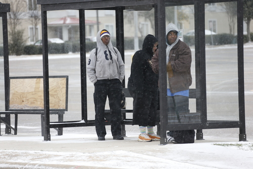 People wait in a bus shelter in north Jackson, Miss., Tuesday, Jan. 28, 2014 as ice and snow flurries cause difficult driving conditions. A severe winter storm is expected to hit the state bringing ice and snow to the Gulf Coast. (AP Photo/Rogelio V. Solis)