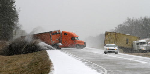 A truck slides as he tries to avoid another wrecked truck as snow begins to accumulate on I-65 several road closures in Alabama on Tuesday, Jan. 28, 2014, in Clanton, Ala. (AP Photo/Butch Dill)