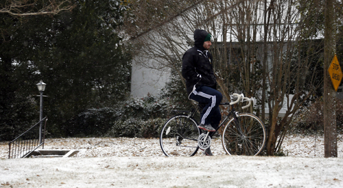 A cyclist tries rides without his hands in north Jackson, Miss., Tuesday, Jan. 28, 2014. An arctic blast spread across Mississippi with below freezing temperatures and treacherous driving conditions. (AP Photo/Rogelio V. Solis)