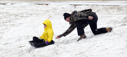 A parent gives his child a push down the hills that surround the soccer fields at Belhaven University in Jackson, Miss., Tuesday, Jan. 28, 2014. An arctic blast spread across Mississippi with below freezing temperatures and treacherous driving conditions. (AP Photo/Rogelio V. Solis)