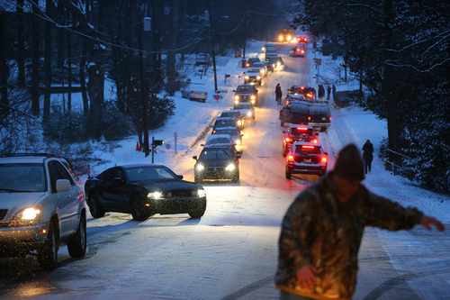 Dozens of motorists become standed on Womack Road as dropping temperatures turn the hill into a sheet of ice on Tuesday night Jan. 28, 2014, in Dunwoody, Georgia.  Georgia Gov. Nathan Deal says that he will send troopers to schools where students are stranded because they could not make it home on clogged roads caused by the rare snowstorm. The governor spoke from the Capitol building Tuesday night.  (AP Photo/Atlanta Journal-Constitution, Curtis Compton)