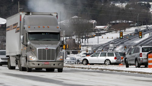 Icy conditions and abandoned  vehicles has traffic at a stand still along Highway 280 on Wednesday, Jan. 29, 2014, in Inverness, Ala. A Winter storm caught much of Alabama off guard and stranded thousands of people at work, schools and on roadways. (AP Photo/Butch Dill)