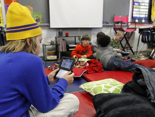 Gavin Chambers plays an electronic game at Oak Mountain Intermediate school on Wednesday, Jan. 29, 2014, in Indian Springs, Ala. About 80 children  and 20 adults spent the night at the school due to a winter storm.  Overnight, the South saw fatal crashes and hundreds of fender-benders. Jackknifed 18-wheelers littered Interstate 65 in central Alabama. (AP Photo/Butch Dill)