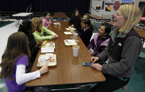 Art teacher, Leigh Walker, entertains students over breakfast that spent the night at Oak Mountain Intermediate school on Wednesday, Jan. 29, 2014, in Indian Springs, Ala. About 80 children and 20 adults spent the night at the school due to a winter storm.  Tuesday's storm deposited mere inches of snow, barely enough to qualify as a storm up North. And yet it was more than enough to paralyze the Deep South. (AP Photo/Butch Dill)