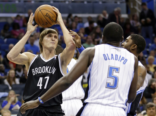 Brooklyn Nets' Andrei Kirilenko (47), of Russia, looks to pass the ball as he is defended by the Orlando Magic defense including Victor Oladipo (5) during the first half of an NBA basketball game in Orlando, Fla., Sunday, Nov. 3, 2013. (AP Photo/John Raoux)