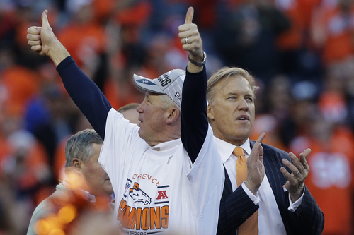 Denver Broncos head coach John Fox and Vice President John Elway celebrate during the trophy presentation after the AFC Championship NFL playoff football game against the New England Patriots in Denver, Sunday, Jan. 19, 2014. The Broncos defeated the Patriots 26-16 to advance to the Super Bowl. (AP Photo/Julie Jacobson)