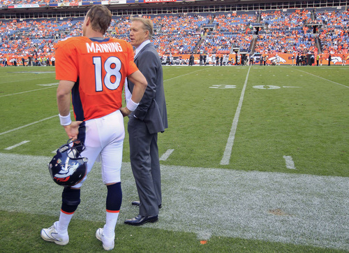 FILE - In this Sunday, Sept. 30, 2012, Denver Broncos' executive vice president of football operations John Elway, right, talks with quarterback Peyton Manning  during the fourth quarter of an NFL football game against the Oakland Raiders in Denver. Elway says doesn't see Manning riding off into the sunset if Manning caps his record-setting season with his second Super Bowl ring like he did 15 years ago. (AP Photo/David Zalubowski, File)