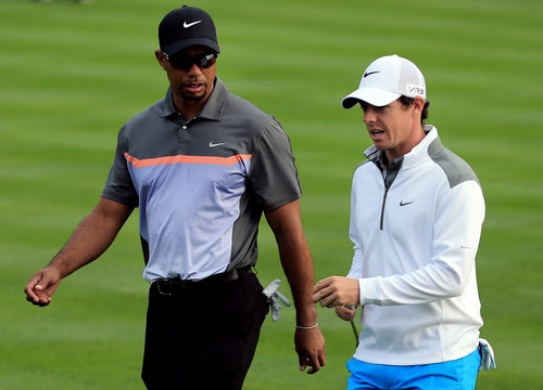 Tiger Woods from the U.S., left, talks to Rory McIlroy of Northern Ireland during the first round of the Dubai Desert Classic golf tournament in Dubai, United Arab Emirates, Thursday, Jan. 30, 2014. (AP Photo)