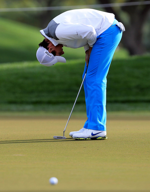 Rory McIlroy of Northern Ireland reacts after missing a putt during the first round of the Dubai Desert Classic golf tournament in Dubai, United Arab Emirates, Thursday, Jan. 30, 2014. (AP Photo)