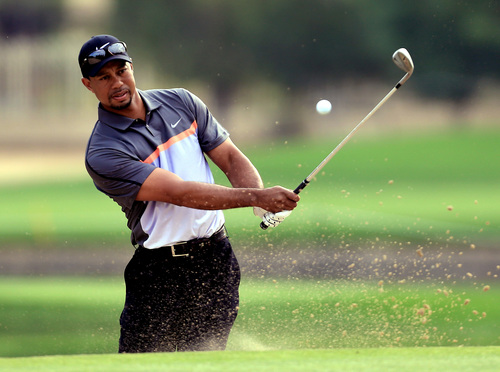 Tiger Woods from the U.S., left, hits a bunker during the first round of the Dubai Desert Classic golf tournament in Dubai, United Arab Emirates, Thursday, Jan. 30, 2014. (AP Photo)