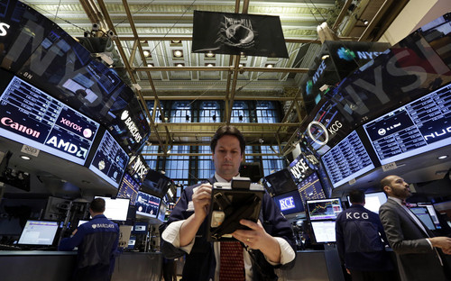 FILE - In this Thursday, Jan. 30, 2014, file photo, Trader Patrick McKeon, center, works on the floor of the New York Stock Exchange. (AP Photo/FILE)