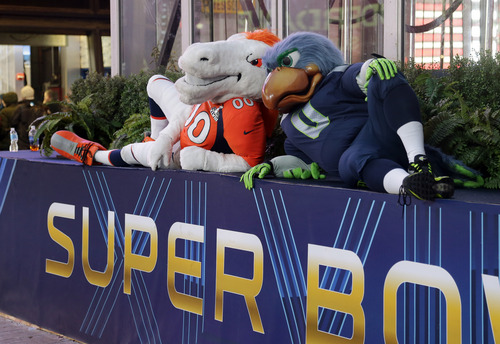 Blitz, right, the Seattle Seahawks mascot, is sits with Miles, left, the Denver Broncos mascot, Friday, Jan. 31, 2014 on top of a Super Bowl sign during a live broadcast of Good Morning America at Times Square in New York. The Seattle Seahawks will play the Broncos Sunday in the NFL Super Bowl XLVIII football game in East Rutherford, N.J. (AP Photo/Ted S. Warren)