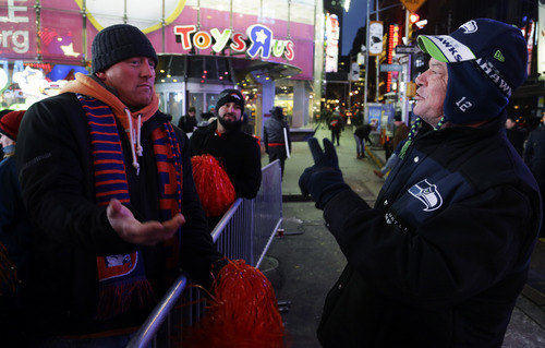 Seattle Seahawks fan Lynn Thomas, right, of Seattle, jokes with Denver Broncos fan Aaron Cassel, left, of Denver, Colo., about the possible outcome of the Super Bowl, Friday, Jan. 31, 2014 at Times Square in New York. The Seattle Seahawks will play the Broncos Sunday in the NFL Super Bowl XLVIII football game in East Rutherford, N.J. (AP Photo/Ted S. Warren)