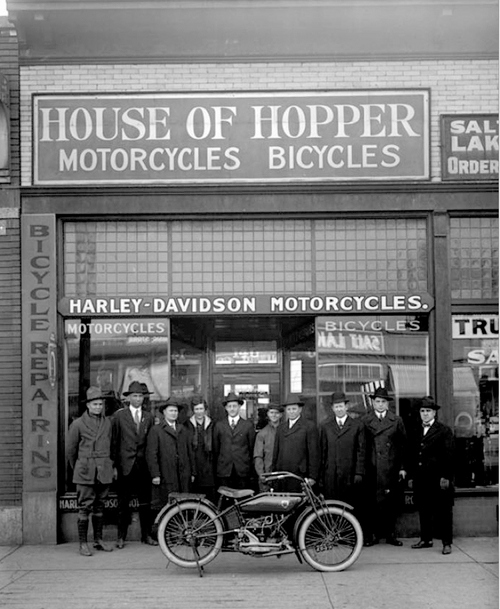 Photos courtesy of Utah Historical Society  Image shows a group of men standing in front of the House of Hopper motorcycle and bicycle shop on 300 South, January 25, 1919. They are showing off a brand new motorcycle..