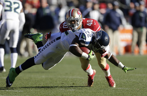 Seattle Seahawks running back Robert Turbin (22) is stopped with the ball by San Francisco 49ers defensive back Darryl Morris (40) in the first half of an NFL football game, Sunday, Dec. 8, 2013, in San Francisco. (AP Photo/Marcio Jose Sanchez)