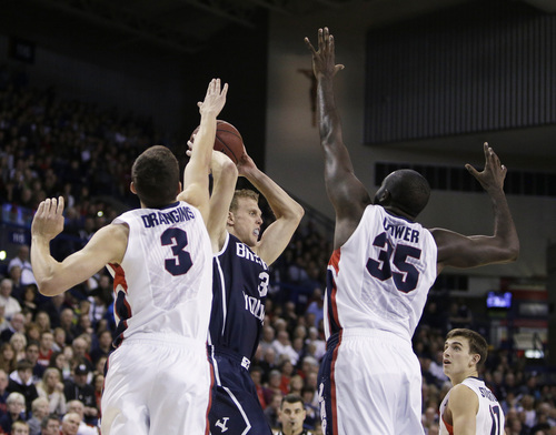 BYU's Tyler Haws (3) looks for a teammate to pass as Gonzaga's Kyle Dranginis (3) and Sam Dower Jr. (35) defend during the first half of an NCAA college basketball game Saturday, Jan. 25, 2014, in Spokane, Wash. (AP Photo/Young Kwak)