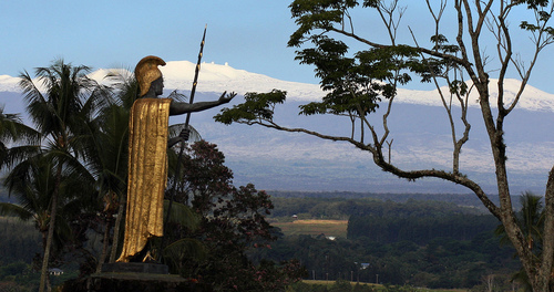 Snow on Mauna Kea is seen Friday Jan. 31, 2014, behind a statue of the Hawaiian King Kamehameha in Hilo, Hawaii.  (AP Photo/Tim Wright)