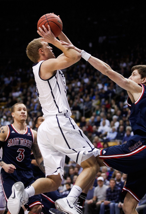 BYU's Tyler Haws, left, is fouled by Saint Mary's Dane Pineau, right, during the NCAA basketball game between Brigham Young University and Saint Mary's at the Marriott Center in Provo on Saturday, Feb. 1, 2014. (AP Photo/The Daily Herald, Spenser Heaps)