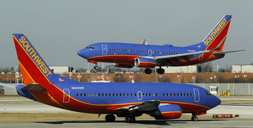 In this Feb. 9, 2012 file photo, a Southwest Airlines Boeing 737 waits to take off at Chicago's Midway Airport as another lands.  (AP Photo/Charles Rex Arbogast)