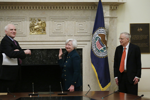 Janet Yellen, accompanied by her husband, Nobel Prize winning economist, George Akerlof, right, is administered the oath of office as Federal Reserve Board chair by Fed Board Gov. Daniel K. Tarullo, Monday, Feb. 3, 2014, at the Federal Reserve in Washington. Yellen is the first woman to lead the Federal Reserve. (AP Photo/Charles Dharapak)