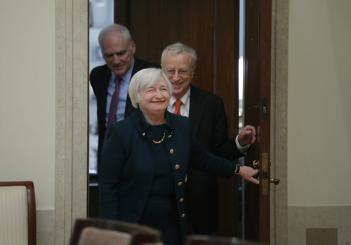 Janet Yellen, followed by her husband, Nobel Prize winning economist George Akerlof and Fed Board Gov. Daniel K. Tarullo, smiles as she walks into a room of applause by staff members before she is administered the oath of office as Federal Reserve Board chair, Monday, Feb. 3, 2014, at the Federal Reserve in Washington. Yellen is the first woman to lead the Federal Reserve.  (AP Photo/Charles Dharapak)