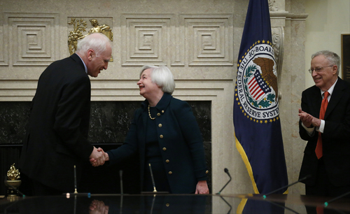 Janet Yellen shakes hands with Fed Board Gov. Daniel K. Tarullo, left, after she was administered the oath of office as Federal Reserve Board chair, Monday, Feb. 3, 2014, at the Federal Reserve in Washington. Yellen's husband, Nobel Prize winning economist George Akerlof applauds at right. Yellen, is the first woman to lead the Federal Reserve.  (AP Photo/Charles Dharapak)