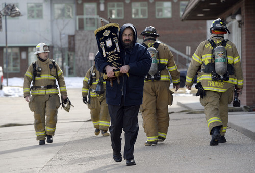 Francisco Kjolseth  |  The Salt Lake Tribune Rabbi Benny Zippel removes one of two Torah scrolls for safekeeping after smelling smoke and calling the fire department to the Chabad Lubavitch of Utah Jewish center at 1760 S. 1100 East in Salt Lake City on Monday, Feb. 3, 2014. Several children from the day care were safely removed while the cause of the smoke is under investigation.
