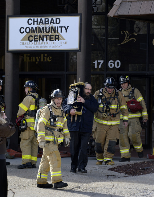 Francisco Kjolseth  |  The Salt Lake Tribune Rabbi Benny Zippel removes one of two Torah scrolls for safekeeping after smelling smoke and calling the fire department to the Chabad Community Center at 1760 South 1100 East in Salt Lake City on Monday, Feb. 3, 2014. The cause of the smoke is under investigation.