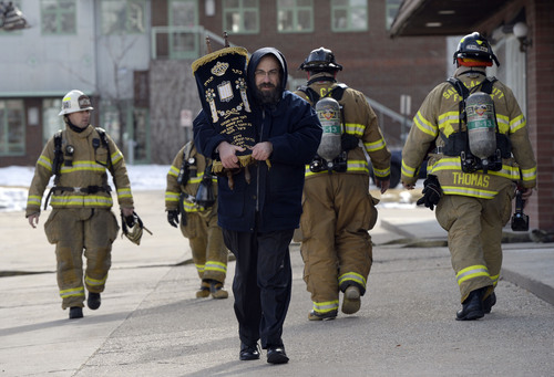 Francisco Kjolseth  |  The Salt Lake Tribune Rabbi Benny Zippel removes one of two Torah scrolls for safekeeping after smelling smoke and calling the fire department to the Chabad Lubavitch of Utah Jewish center at 1760 South 1100 East in Salt Lake City on Monday, Feb. 3, 2014. Several children from the daycare were safely removed while the cause of the smoke is under investigation.