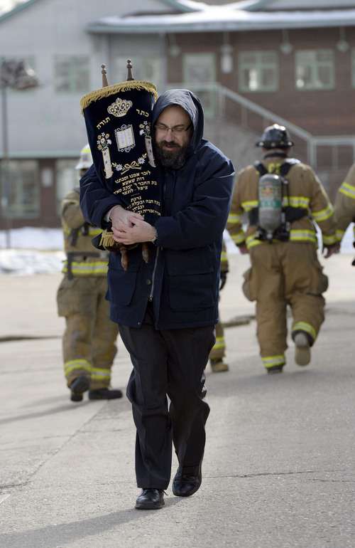 Francisco Kjolseth  |  The Salt Lake Tribune Rabbi Benny Zippel removes one of two Torah scrolls for safekeeping after smelling smoke and calling the fire department to the Chabad Lubavitch of Utah Jewish center at 1760 S. 1100 East in Salt Lake City on Monday, Feb. 3, 2014. Several children from a day care in the building were safely removed while the cause of the smoke is under investigation.