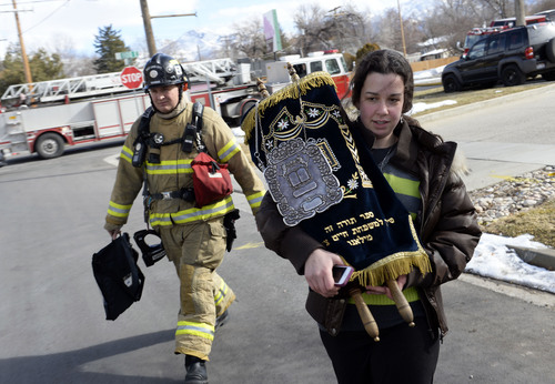 Francisco Kjolseth  |  The Salt Lake Tribune Chaya Zippel, 18, removes one of two Torah scrolls for safekeeping after smoke was detected at the Chabad Lubavitch of Utah Jewish center at 1760 S. 1100 East in Salt Lake City on Monday, Feb. 3, 2014. Several children froma day care in the building were safely removed while the cause of the smoke is under investigation.