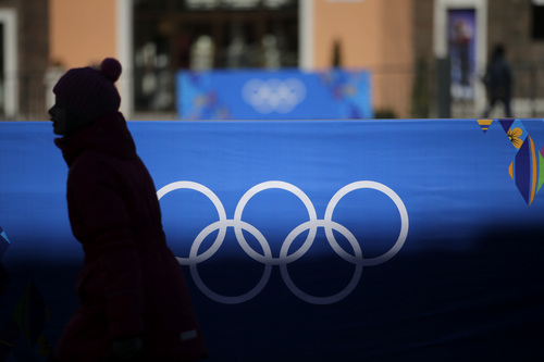 A girl walks past a banner showing the Olympic rings on Monday, Feb. 3, 2014, in Krasnaya Polyana, Russia, as preparations for the 2014 Winter Olympics continue. (AP Photo/Jae C. Hong)