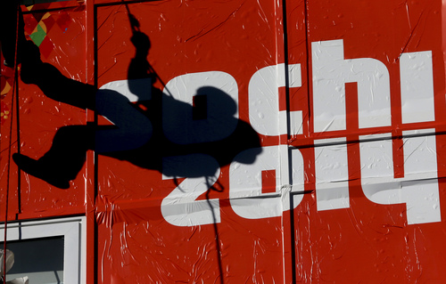 A worker climbs past an Olympic logo at the ski jumping venue during preparations for the 2014 Winter Olympics, Monday, Feb. 3, 2014, in Krasnaya Polyana, Russia. (AP Photo/Dmitry Lovetsky)