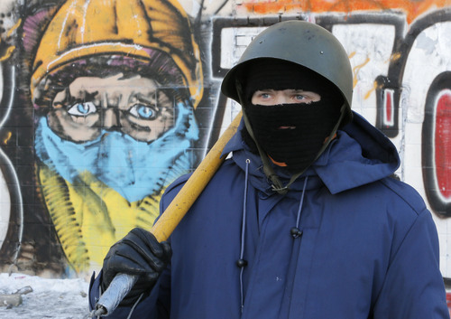 """An opposition activist stands near a wall covered in graffiti with the writing """"Revolution""""  close to barricades in central Kiev, Ukraine, Monday, Feb. 3, 2014. Ukraine's president will return Monday from a short sick leave that had sparked a guessing game as to whether he was taking himself out of action in preparation to step down or for a crackdown on widespread anti-government protests. (AP Photo/Efrem Lukatsky)"""