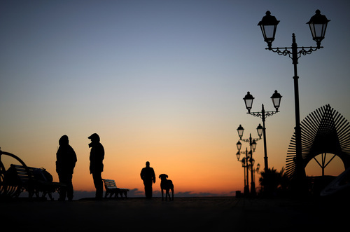 Police patrol along the boardwalk on the Black Sea accompanied by a stray dog outside the Olympic Park at the 2014 Winter Olympics, Monday, Feb. 3, 2014, in Sochi, Russia. (AP Photo/David Goldman)