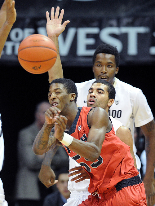 Utah;'s Delon Wright, foreground, gets a pass away as Colorado's Xavier Talton, center, and Wesley Gordon defend during the first half of an NCAA college basketball game Saturday, Feb. 1, 2014, in Boulder, Colo. (AP Photo/The Daily Camera, Cliff Grassmick) NO SALES