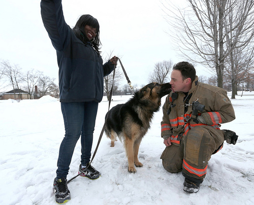Rescue 1 firefighter Michael Paveljack, left, gets a kiss from Mack the dog he rescued  from a sink hole in Buffalo,  N.Y. Sunday Feb. 2, 2014.  Mack fell into the sink hole while he was being walked by his owner Mattie Moore, left, on Sunday  near Martin Luther King, Jr Park.  (AP Photo/The Buffalo News, Robert Kirkham)    TV OUT; MAGS OUT; MANDATORY CREDIT; BATAVIA DAILY NEWS OUT; DUNKIRK OBSERVER OUT; JAMESTOWN POST-JOURNAL OUT; LOCKPORT UNION-SUN JOURNAL OUT; NIAGARA GAZETTE OUT; OLEAN TIMES-HERALD OUT; SALAMANCA PRESS OUT; TONAWANDA NEWS OUT