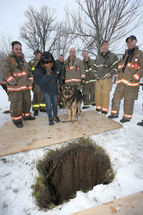 Buffalo, N.Y. Rescue 1 firefighter Michael Paveljack, left,  Mattie Moore, second from,left, and her dog Mack stand by the sink hole where Paveljack rescued Mack on Sunday Feb. 2, 2014 in Buffalo, N.Y.  Mack fell in while he was being walked by Moore on Sunday  near Martine Luther King Jr. Park in Buffalo, N.Y.  (AP Photo/The Buffalo News, Robert Kirkham)   TV OUT; MAGS OUT; MANDATORY CREDIT; BATAVIA DAILY NEWS OUT; DUNKIRK OBSERVER OUT; JAMESTOWN POST-JOURNAL OUT; LOCKPORT UNION-SUN JOURNAL OUT; NIAGARA GAZETTE OUT; OLEAN TIMES-HERALD OUT; SALAMANCA PRESS OUT; TONAWANDA NEWS OUT