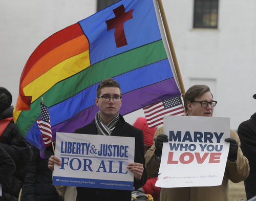 Spencer Geiger, left, of Virginia Beach, and Carl Johanson, of Norfolk, hold signs as they demonstrate outside  Federal Court  in Norfolk, Va., Tuesday, Feb. 4, 2014.  A federal judge heard arguments on whether Virginia's ban on gay marriage is unconstitutional. (AP Photo/Steve Helber)