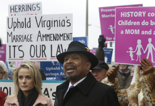 Former Republican candidate for Lt. Gov. E.W. Jackson, front center, speaks to the media during a demonstration outside Federal Court in Norfolk, Va., Tuesday, Feb. 4, 2014. Jackson spoke in favor of the law banning same sex marriage.  A federal judge will hear arguments Tuesday on whether Virginia's ban on gay marriage is unconstitutional. The state's newly elected Democratic attorney general has already decided to side with the plaintiffs and will not defend the ban.  (AP Photo/Steve Helber)