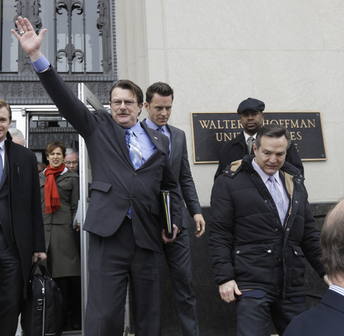 Plaintiff in the Bostic v. Rainey case,  Tony London, waves to the crowd as he and his partner, Tim Bostic, right, leave Federal Court after a hearing on Virginia's ban on gay marriage in Norfolk, Va., Tuesday, Feb. 4, 2014.    A federal judge heard arguments on whether Virginia's ban on gay marriage is unconstitutional. (AP Photo/Steve Helber)