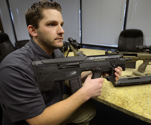 Steve Griffin  |  The Salt Lake Tribune  Seth Ercanbrack, marketing manager for Desert Tech in West Valley City, Utah, with a Micro Dynamic Rifle (MDR) at the company's offices Friday, January 31, 2014. Desert Tech is a Utah gun manufacturer developing one of the more accurate military rifles on the market.