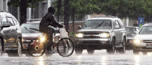 Steve Griffin | The Salt Lake Tribune   A biker gets caught in an afternoon rain shower as it whips through downtown Salt Lake City, Utah Tuesday May 28, 2013.