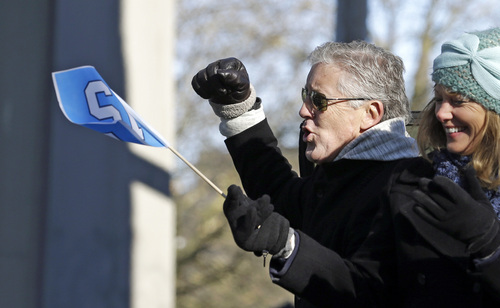 Seattle Seahawks coach Pete Carroll pumps his fist toward spectators at a parade for the NFL football Super Bowl champions Wednesday, Feb. 5, 2014, in Seattle. The Seahawks defeated the Denver Broncos 43-8 on Sunday. (AP Photo/Elaine Thompson)