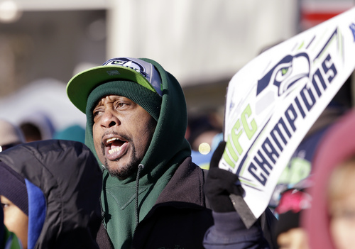 """A Seattle Seahawks fan begins a """"Sea-Hawks"""" cheer while waiting the parade for the Super Bowl champions Wednesday, Feb. 5, 2014, in Seattle. The Seahawks beat the Denver Broncos 43-8 in NFL football's Super Bowl XLVIII on Sunday. (AP Photo/Elaine Thompson)"""