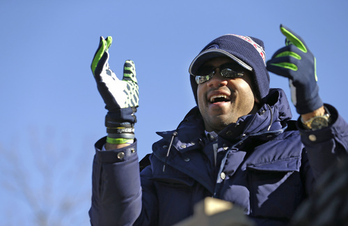 Seattle Seahawks quarterback Russell Wilson applauds fans during a parade for the NFL football Super Bowl champions Wednesday, Feb. 5, 2014, in Seattle. The Seahawks defeated the Denver Broncos 43-8 on Sunday. (AP Photo/Elaine Thompson)
