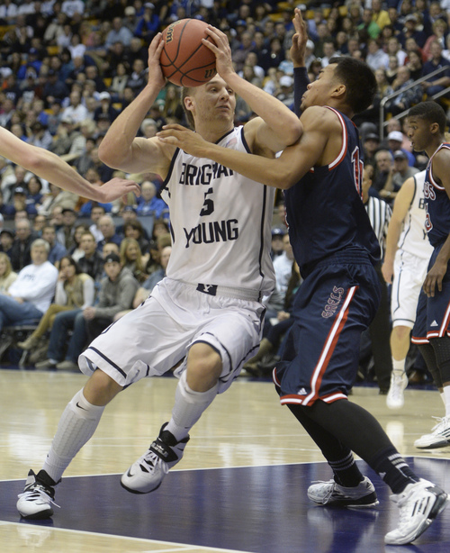 Rick Egan  | The Salt Lake Tribune   Brigham Young Cougars guard Kyle Collinsworth (5) takes the ball insise, as  St. Mary's Gaels guard Stephen Holt (14) defends, in basketball action, BYU vs. St Mary's, at the Marriott Center, Saturday, February 1, 2014.